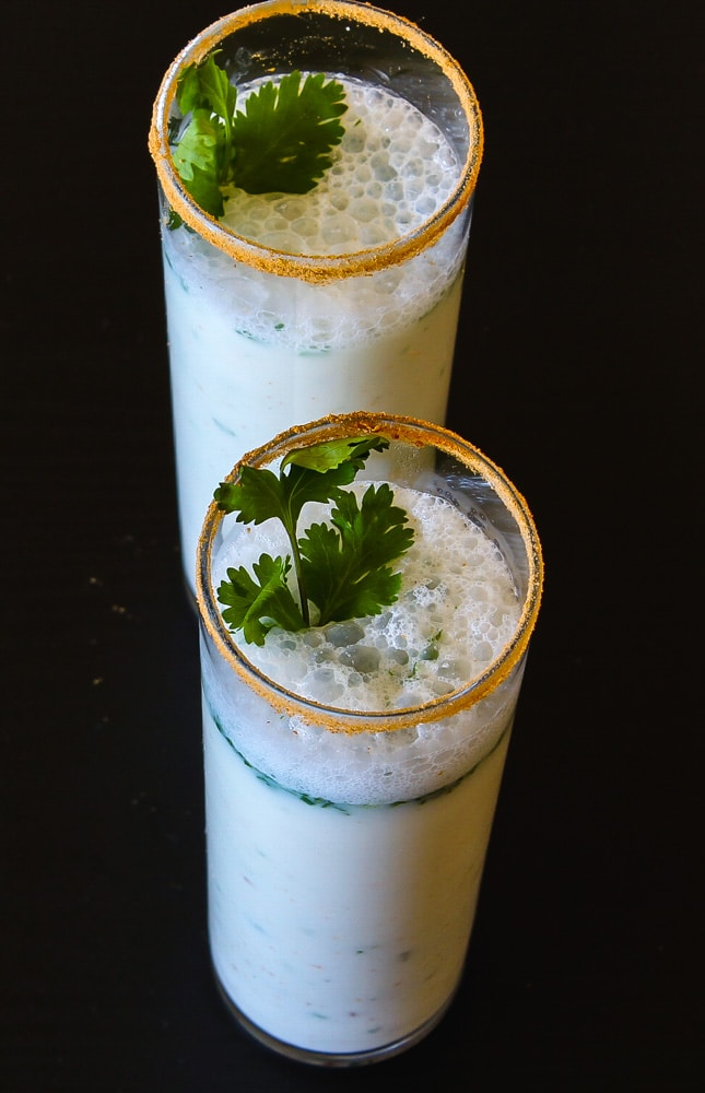 Masala chaas in 2 talls glasses with garnish of cilantro leaves