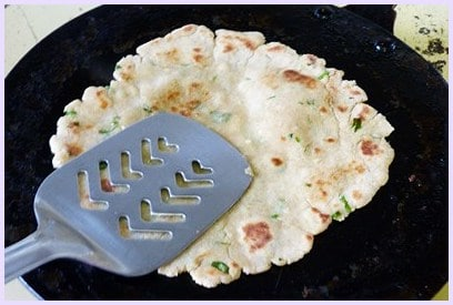 cooking paratha by light pressing with spatula