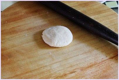 one flatten dough ball on the rolling board