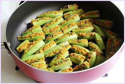 cooking stuffed okra in a pan