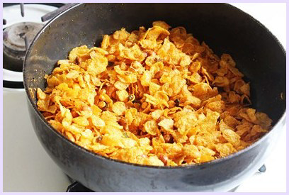 mixing corn flakes well to make namkeen