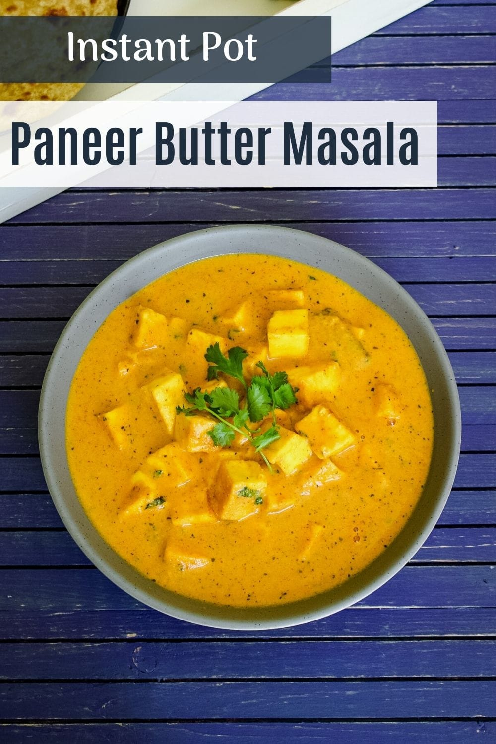 paneer butter masala in a bowl with garnish of cilantro with text on the image of pinterest