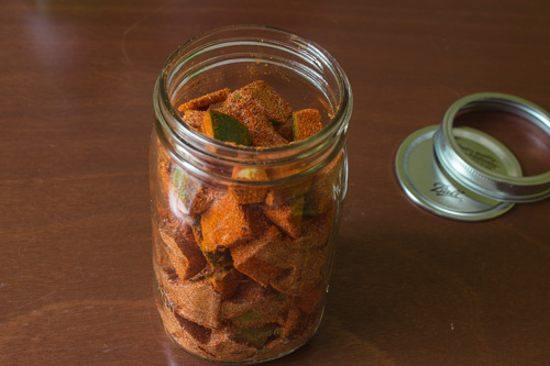 spices coated mangoes added into the glass jar