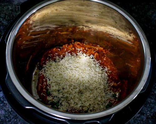 Adding rice to tomato, spice mixture