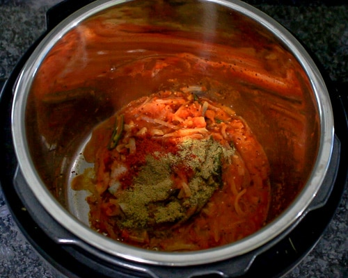 adding spice powders to cooked tomatoes