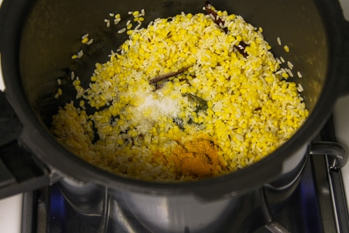 adding soaked dal-rice, salt and turmeric powder in cooker