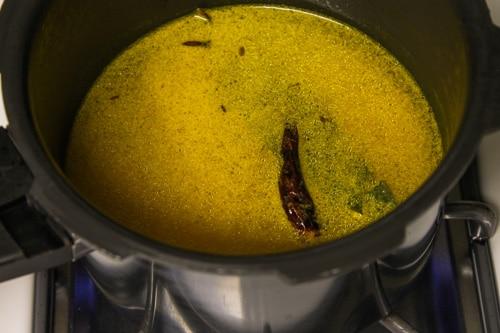 Adding water to make moong dal khichdi