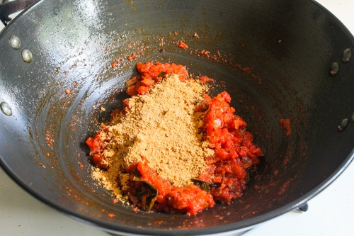 adding freshly ground masala to the tomato mixture