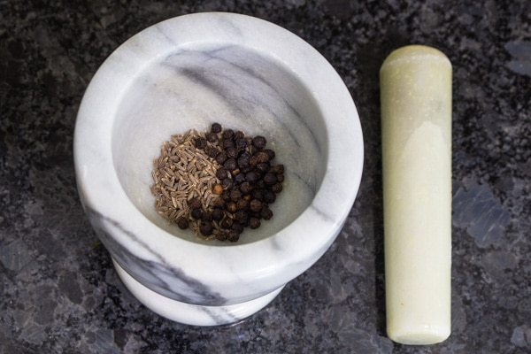 cumin seeds and peppercorns in mortar and pestle
