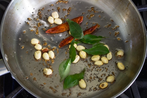 sauteing peanuts, curry leaves and dried red chilies