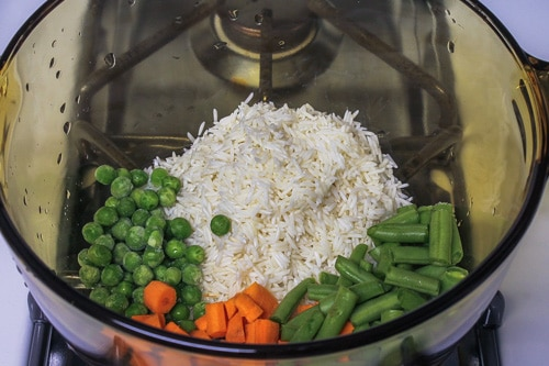 Soaked rice and veggies in a saucepan