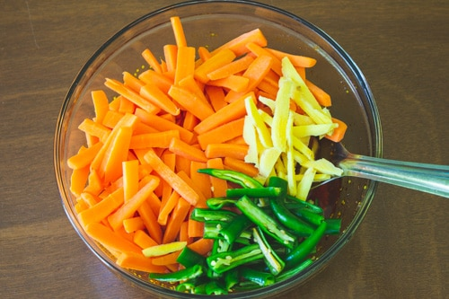 adding carrot, ginger and green chiil to pickle masala
