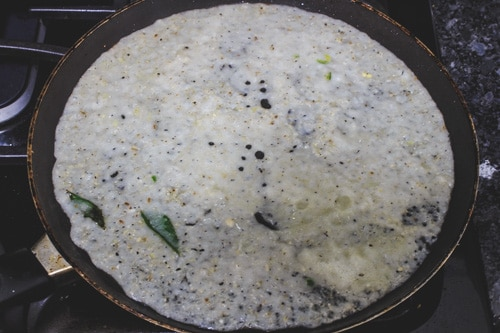 spreading dosa batter in a pan