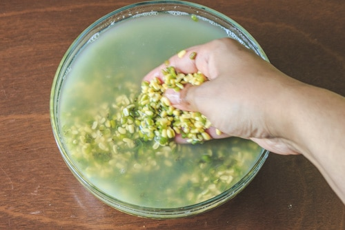 rubbing the dal between fingers