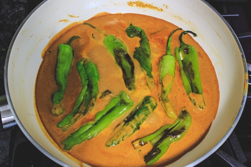 adding chilies to salan gravy