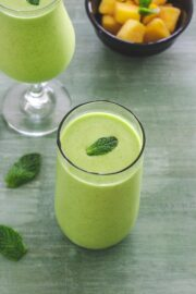 Mango mint smoothie in a glass with mint lead as a garnish
