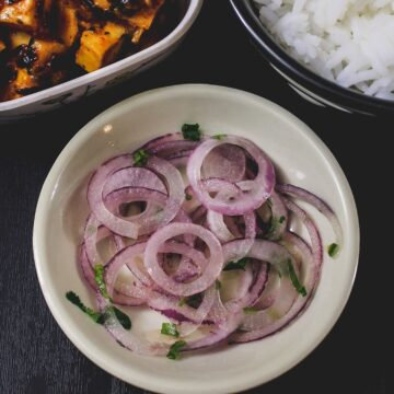 Onion salad in a plate with side of paneer curry and rice