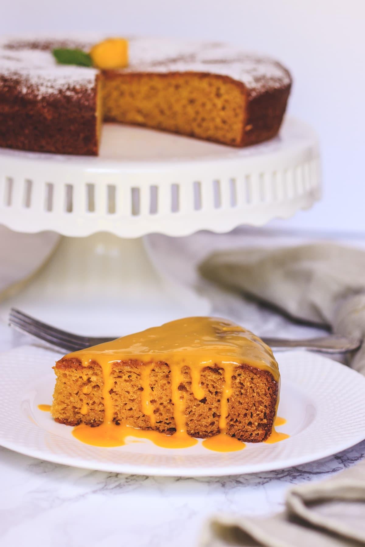 Slice of eggless mango cake with drizzle of mango sauce
