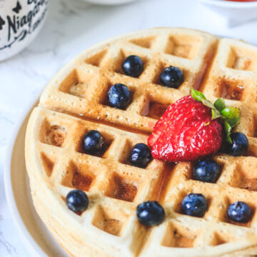 Close up shot of eggless waffles with toppings of berries and maple syrup