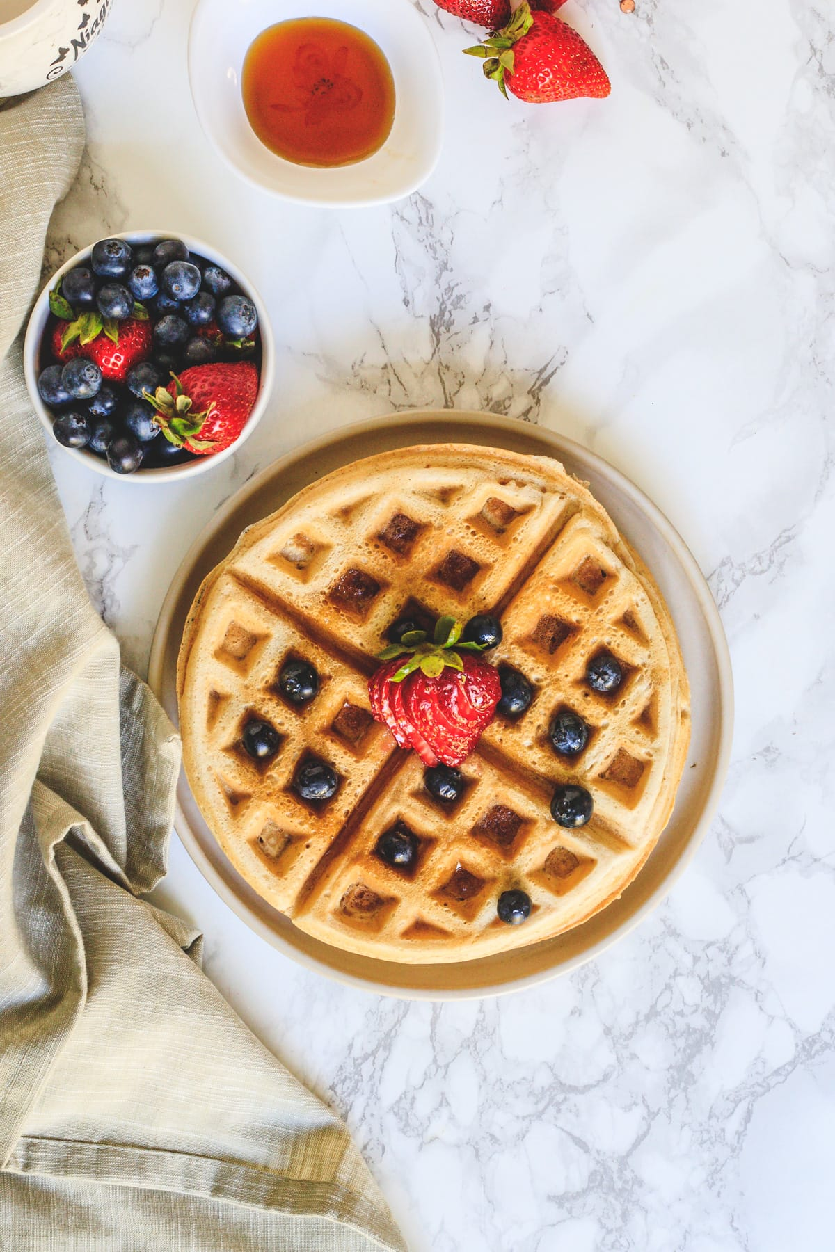 Top view of eggless waffles in a plate with berries