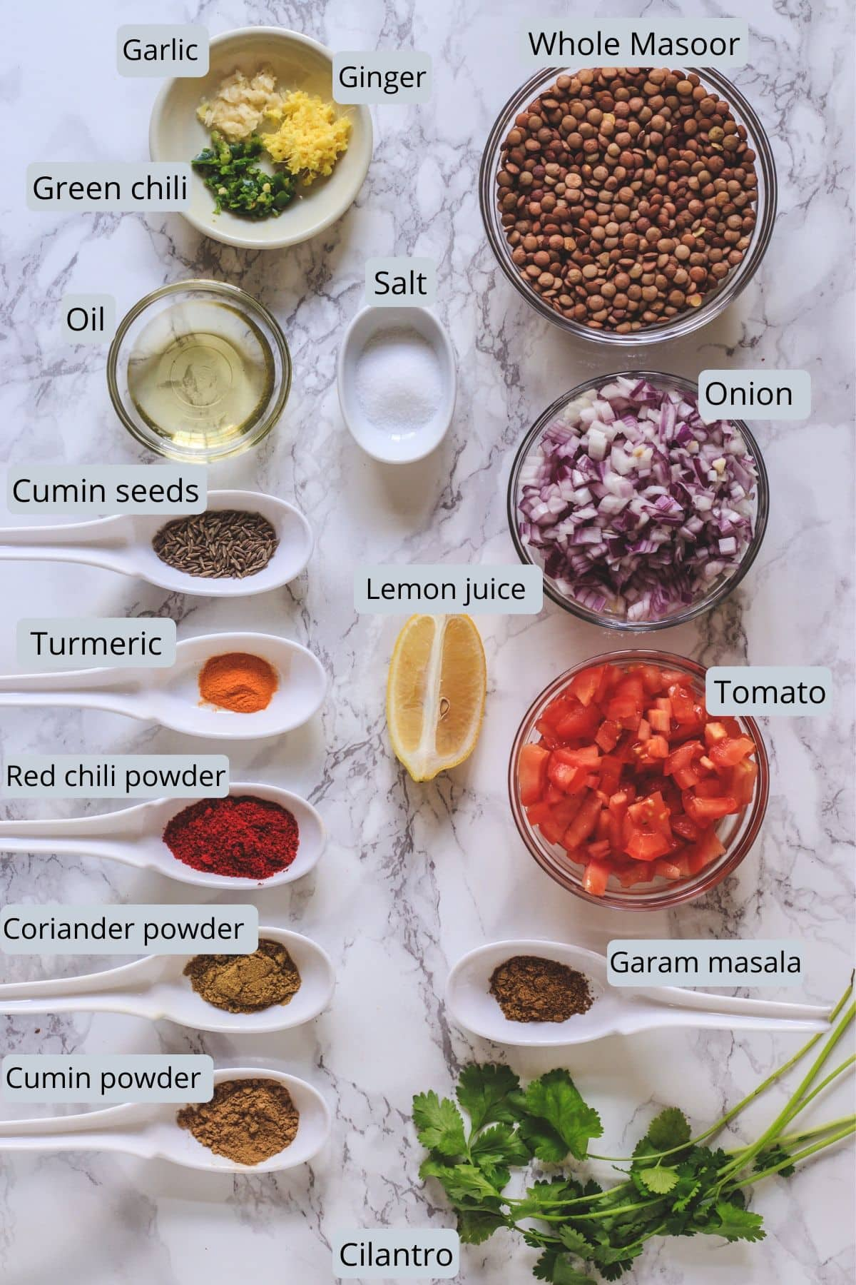 Whole masoor dal recipe ingredients laid down on marble surface