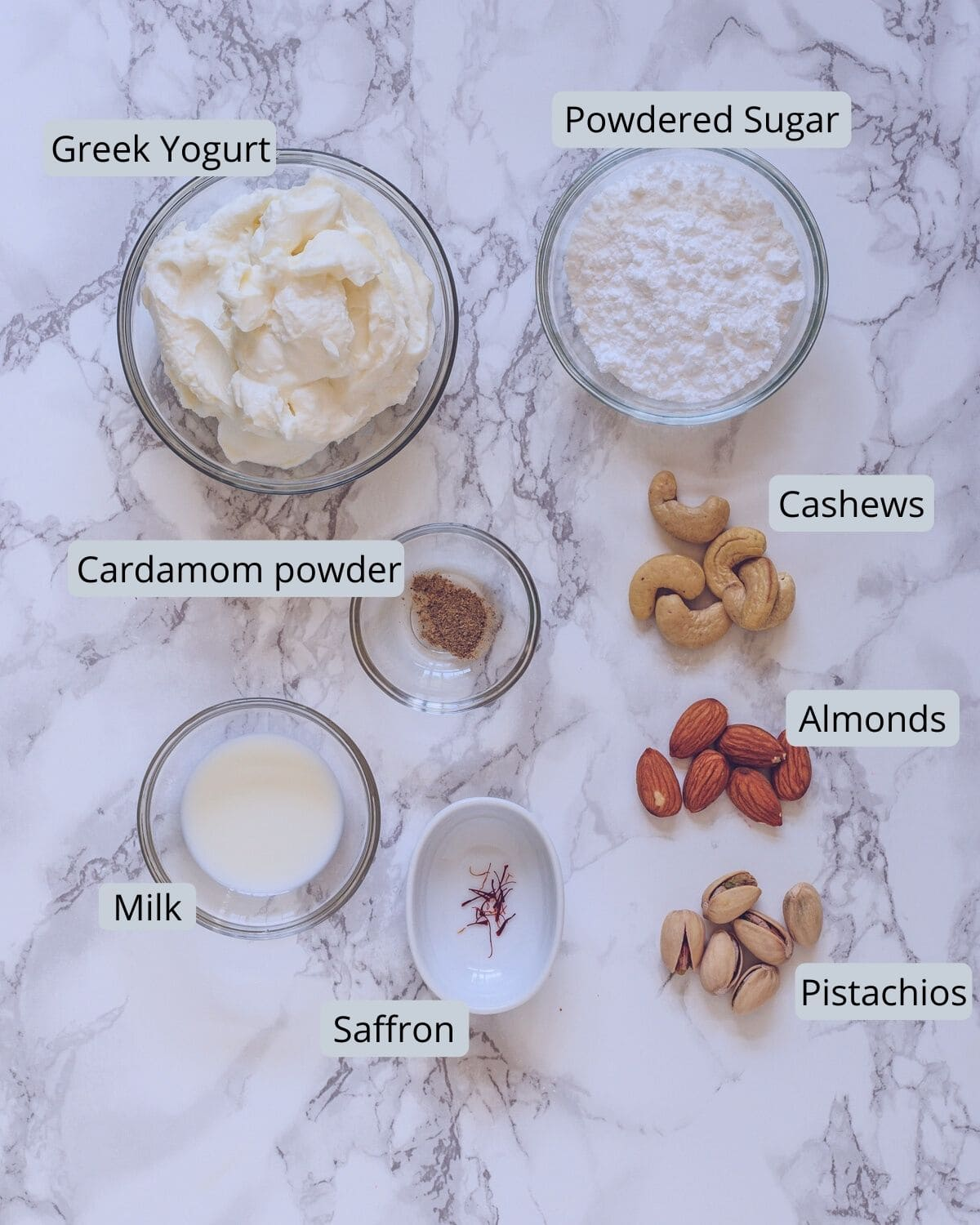 image of ingredients used in shrikhand recipe. Showing greek yogurt, powdered sugar, nuts, milk, saffron, cardamom powder