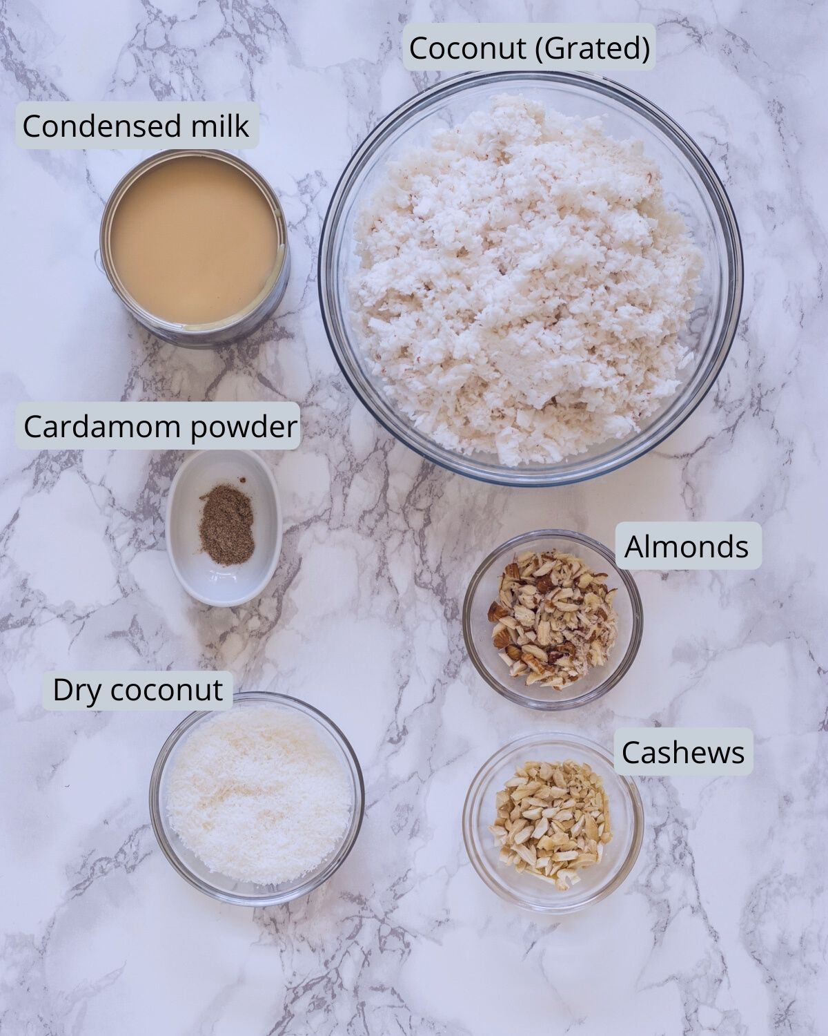 image of ingredients used for coconut ladoo. Includes coconut, condensed milk, cardamom, nuts, dry coconut.