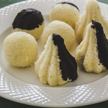 Image of chocolate coated coconut modak and ladoo on a plate
