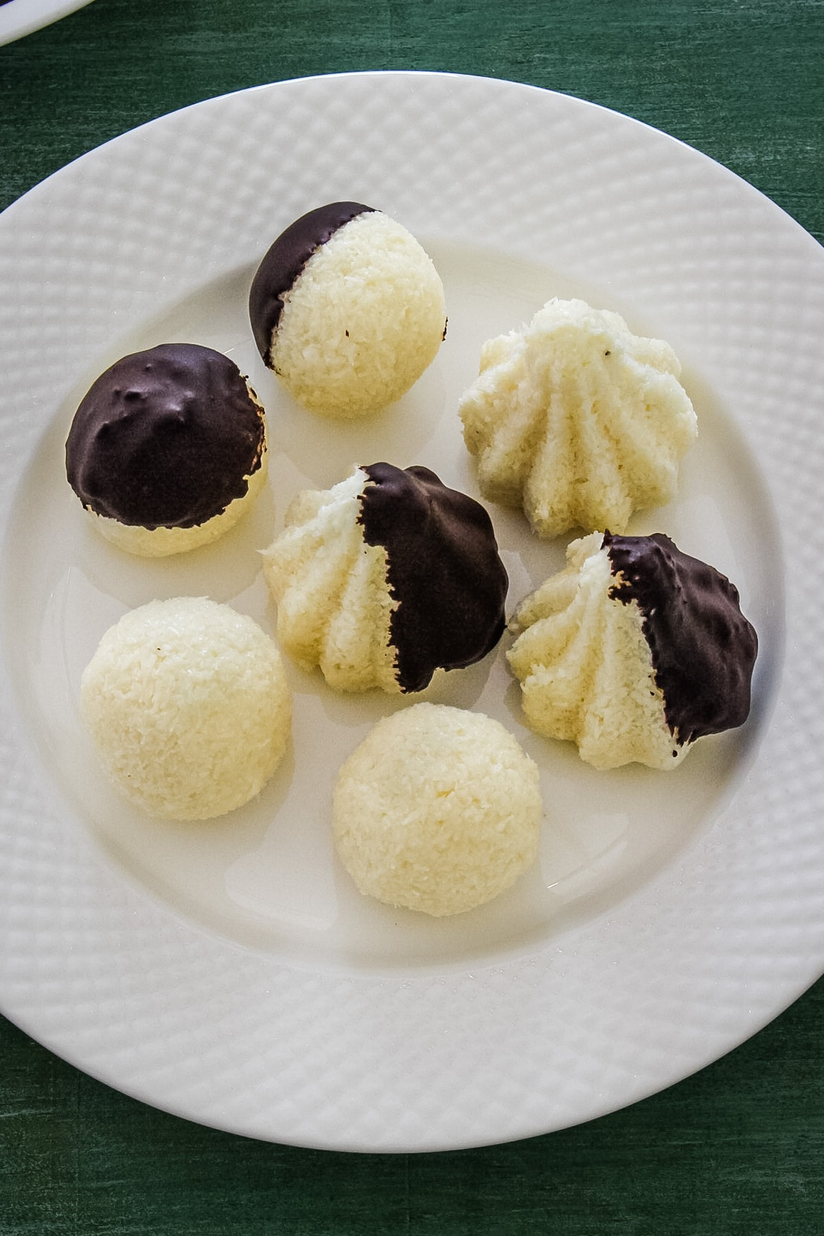 Top view of chocolate coated coconut modak on a white plate