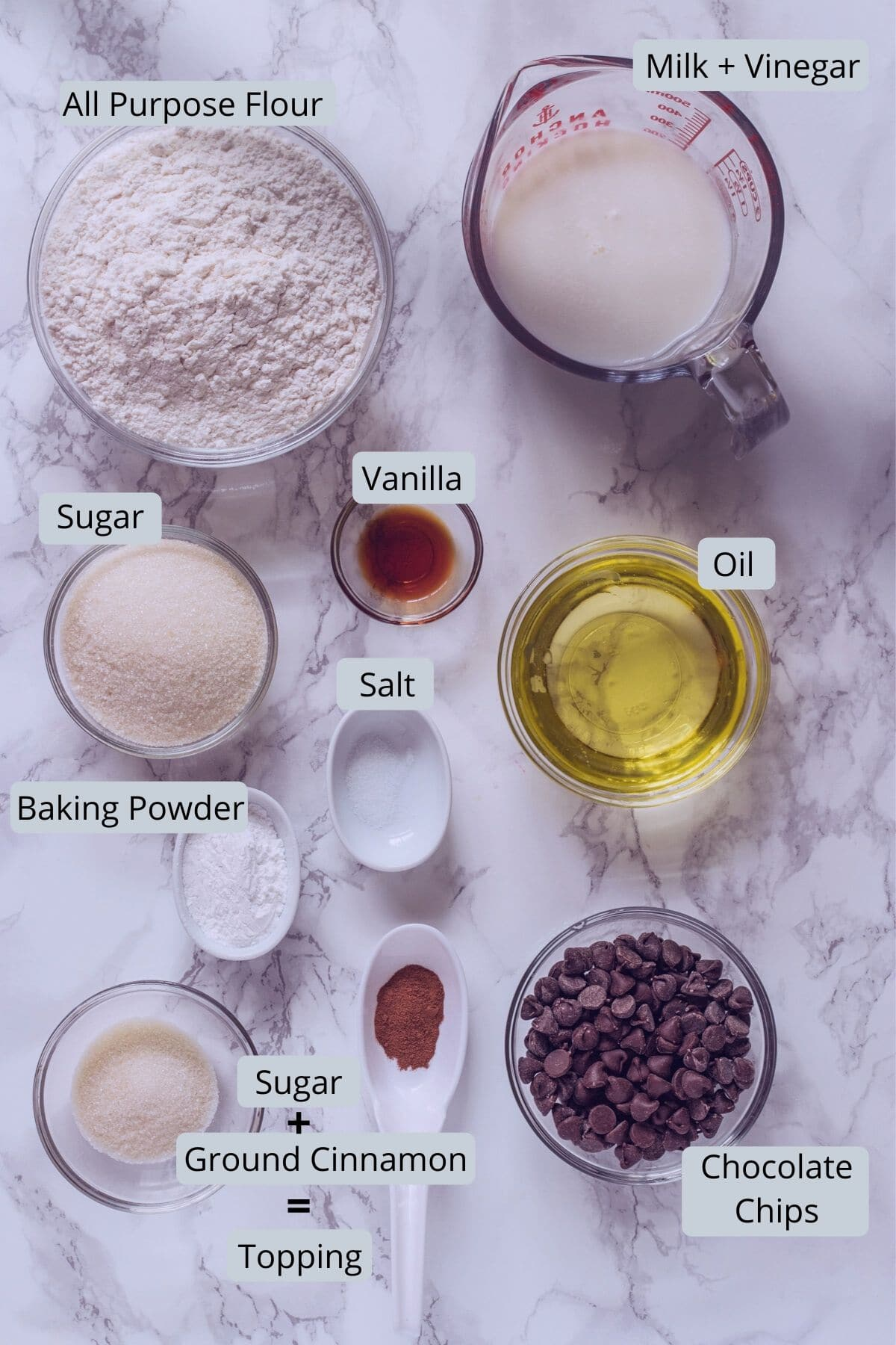 Image of ingredients used in eggless chocolate chip muffins. Includes milk, vinegar, oil, vanilla, flour, sugar, baking powder, salt, chocolate chips