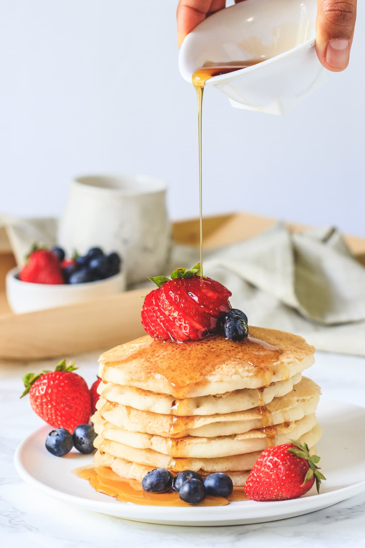 eggless panckes stacked in a plate with garnish of strawberries, blueberries and drizzle of maple syrup