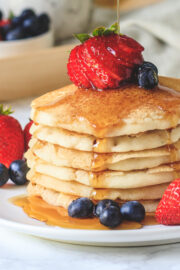 close up of stacked pancakes in a plate with garnish of berries and pouring maple syrup