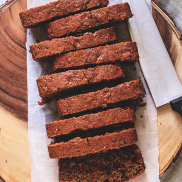 Eggless zucchini bread slices on parchment paper lined wooden tray with knife on side