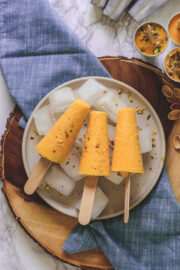 3 Mango Kulfi on ice cubes full of plate & napkin under it