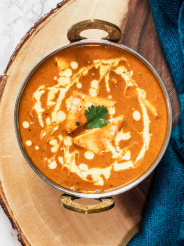 close up top view of shahi paneer in a serving wok on a wooden board