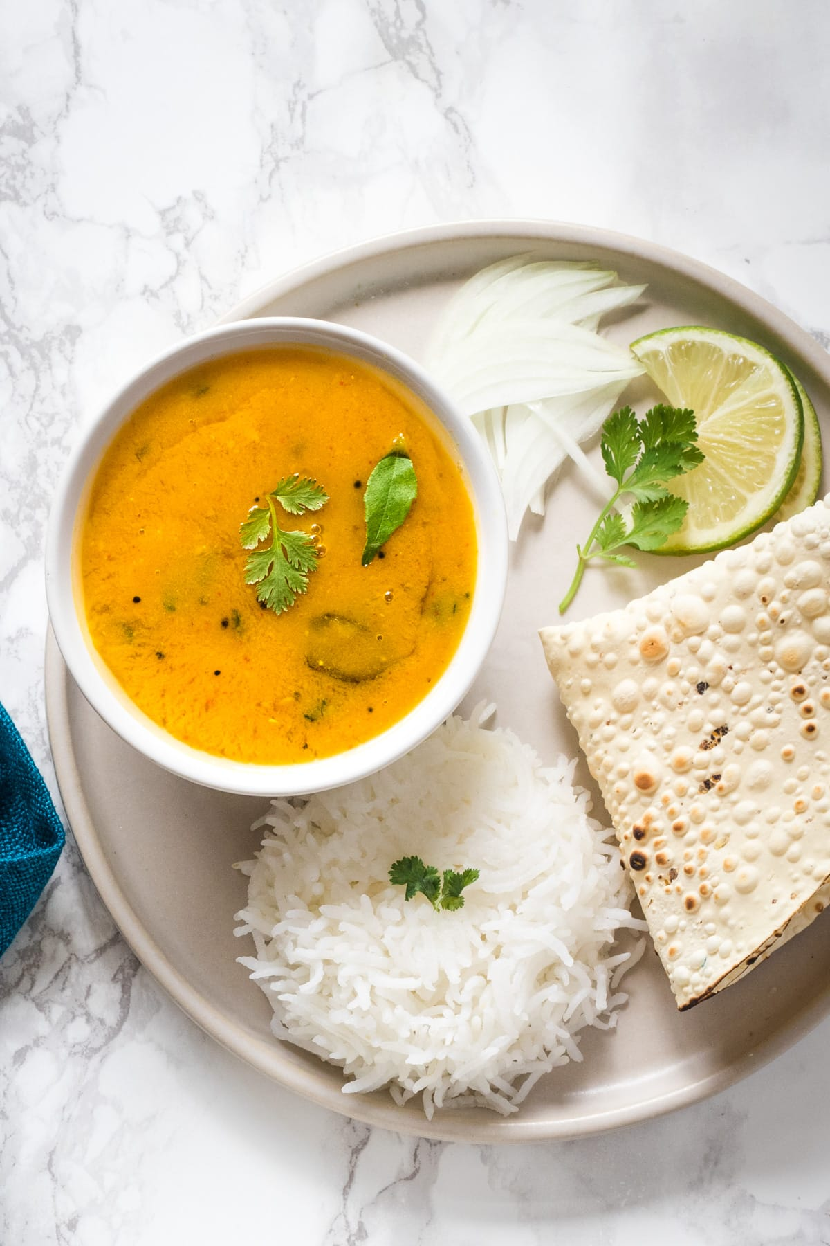 a plate with a bowl of dal, rice, papad, sliced onions and lemon slice with garnish of cilantro leaves.