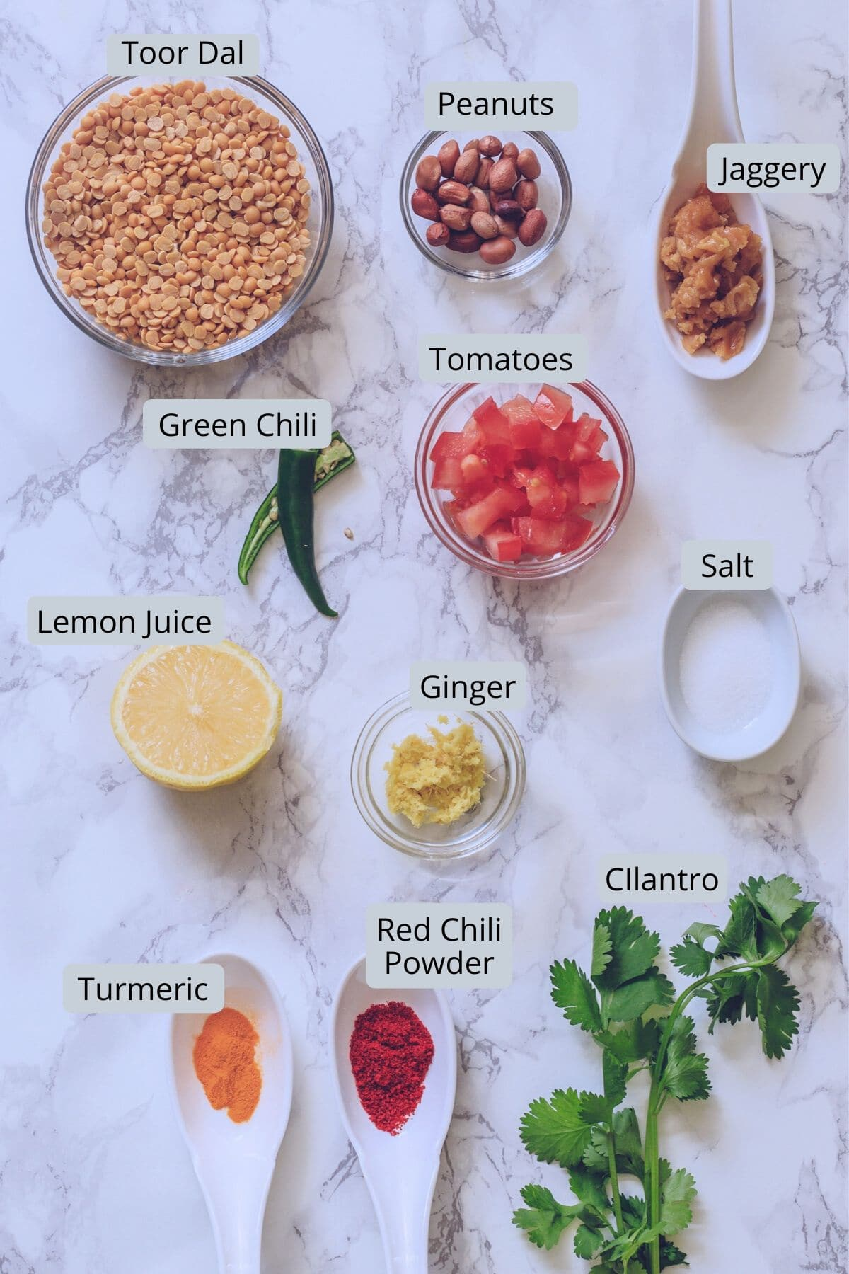 Ingredients used in gujarati dal includes toor dal, peanuts, jaggery, tomatoes, lemon, cilantro, red chili, turmeric powder, salt, ginger, green chili