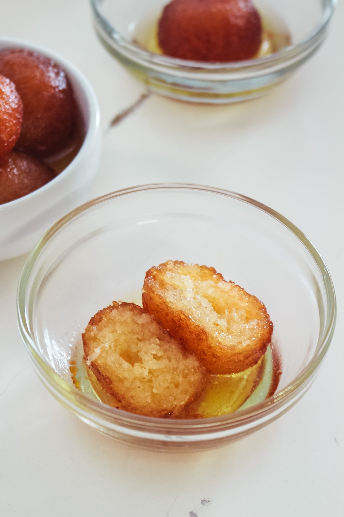 gulab jamun cut into half in a bowl with sugar syrup