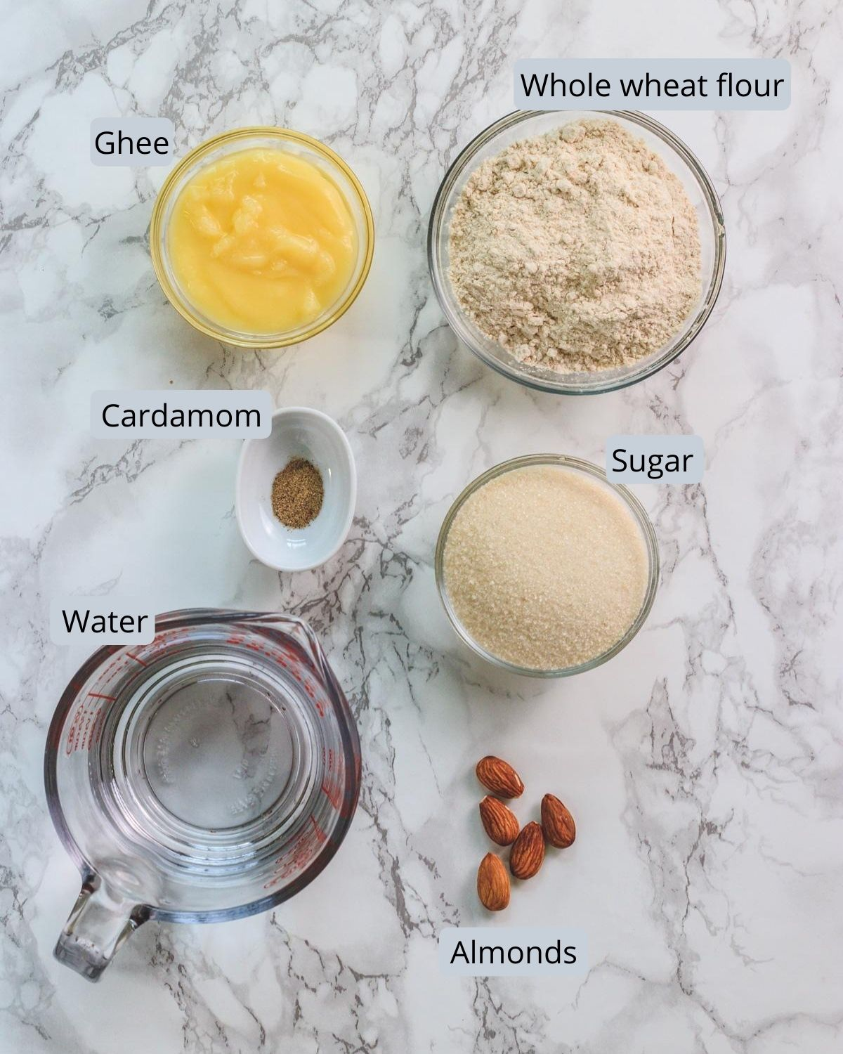 Image of ingredients used in atta hawal includes wheat flour, sugar, ghee, water, cardamom and almonds