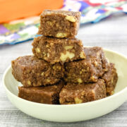 a stack of walnut burfi in a plate with orange container in the back ground
