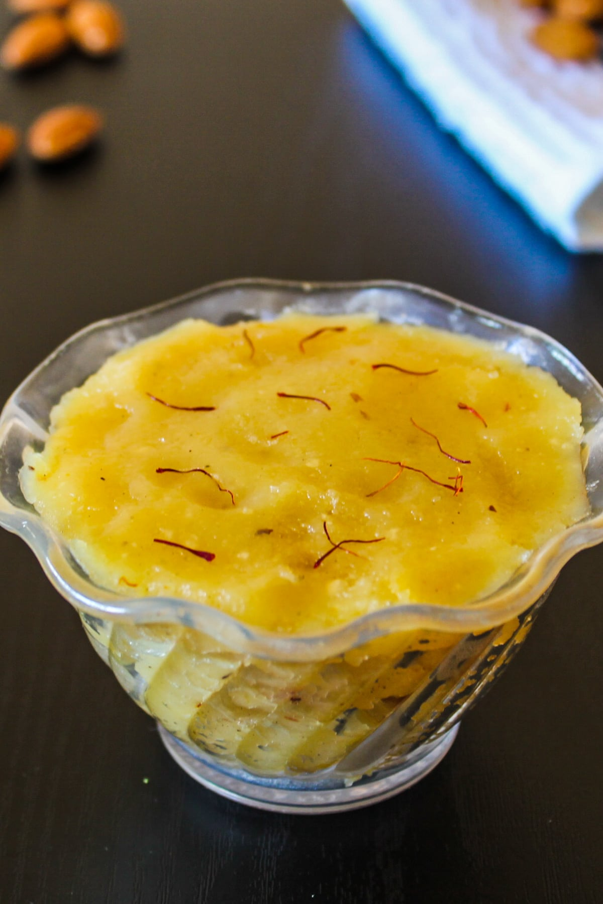 Badam halwa in a bowl garnished with saffron, few whole amonds are in the background