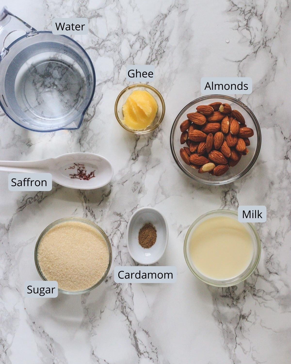 Ingredients used in almond halwa includes almonds, sugar, milk, ghee, saffron, cardamom, water.