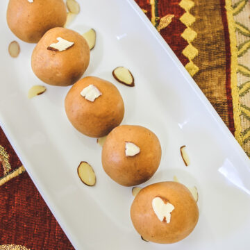 5 besan ladoo garnished with almonds arranged on rectangle plate with decorative napkin underneath