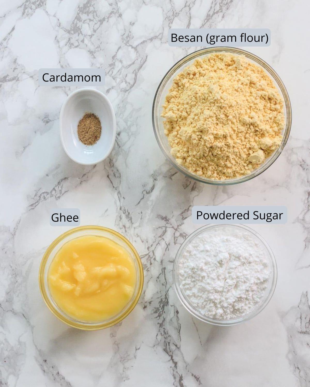 Image of ingredients used in besan ladoo recipe. Includes besan, sugar, cardamom, ghee.