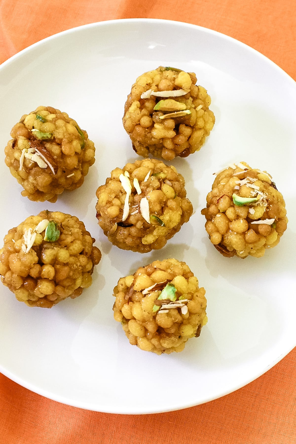 6 boondi ladoo with nuts garnish arranged on white plate with orange linen background