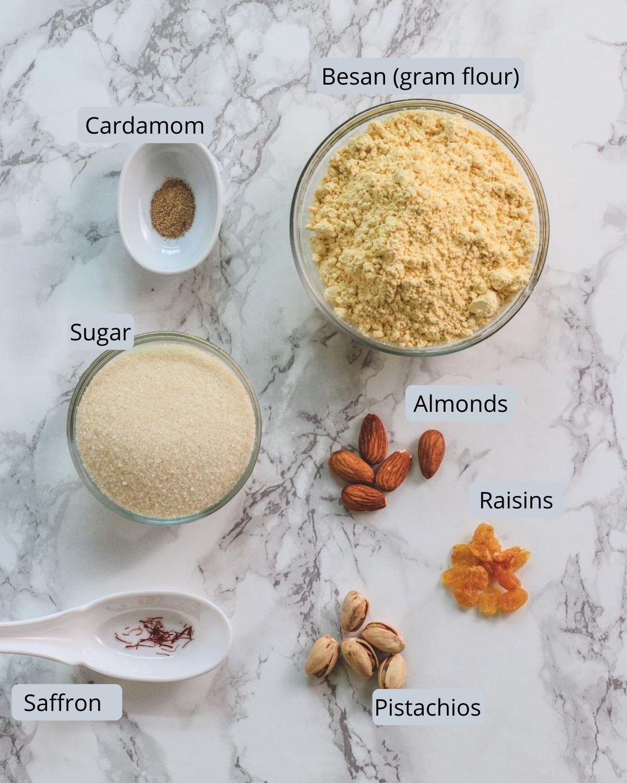 Image of ingredients for boondi ladoo includes besan, sugar, cardamom, saffron, almonds, pistachios, raisins