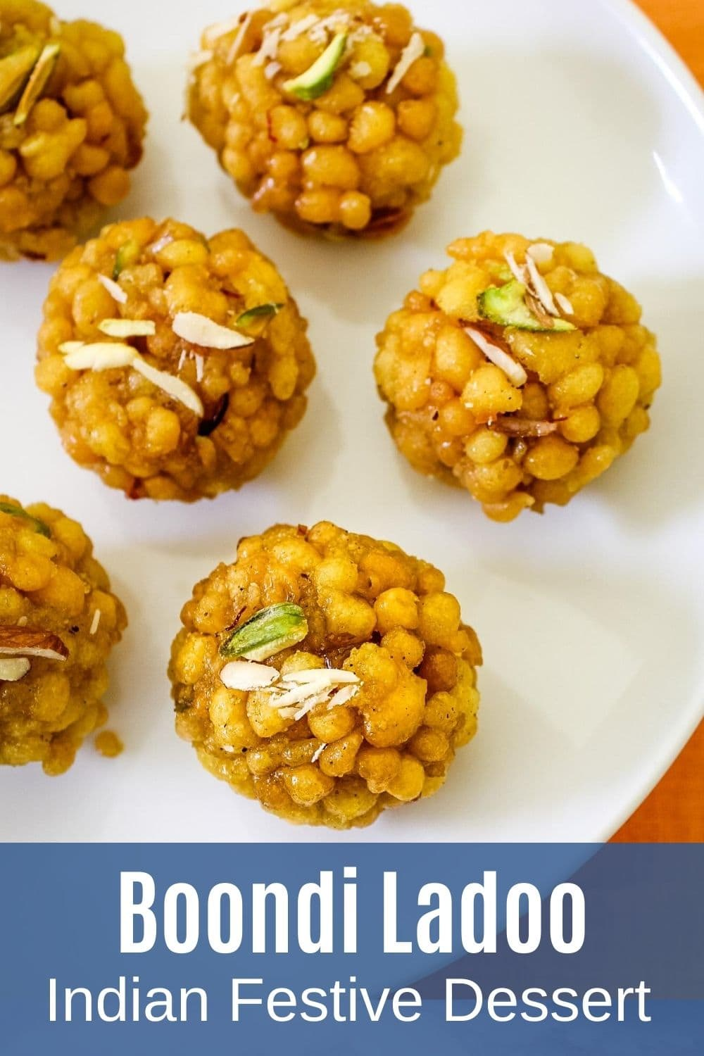 Boondi ladoo on plate garnished with chopped nuts with text at the bottom of the image for pinterest