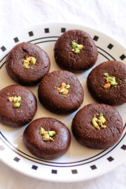 7 chocolate peda arranged on a plate with garnish of chopped pistachios