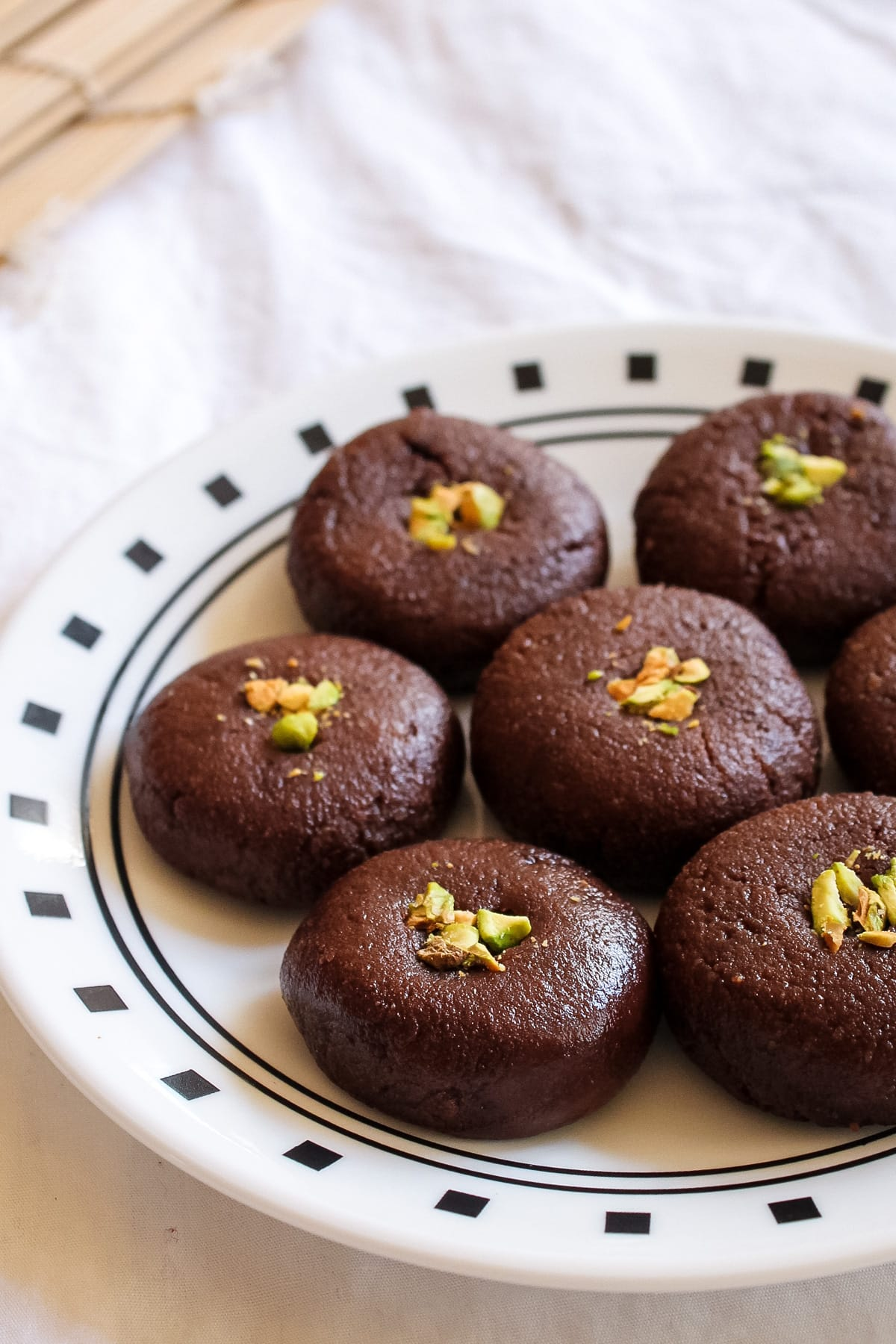 Close up of chocolate peda garnished with chopped pistachio in a plate