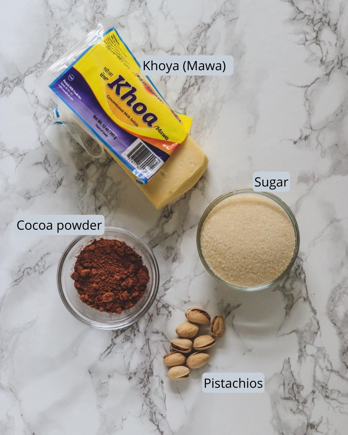image of ingredients used in chocolate peda includes khoya, sugar, cocoa powder and pistachios